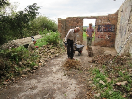 sorting useful stones from brick and cement rubble, rubbbish and nettle roots