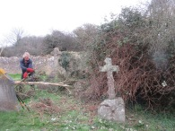 clearing scrub to reveal more grave stones
