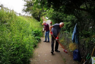 clearing nettles and other weeds and sweeping up